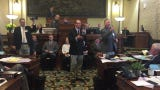 The state Senate auctions off two flags, raising a combined $3,100, to help an injured staff member.