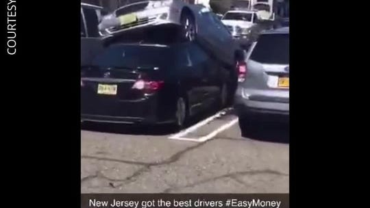 While parking, car drives on top of another car at New Jersey shopping center