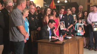 Gov. Doug Ducey signs HB 2318 in the rotunda of the Arizona Capitol Museum on April 22, 2019. The bill prohibits talking or texting on a phone in AZ.