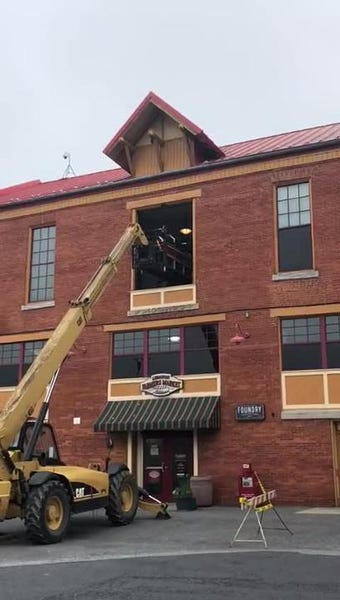 A crane begins to remove a 2,000 pound grill form the third floor of the Lebanon Farmers Market.