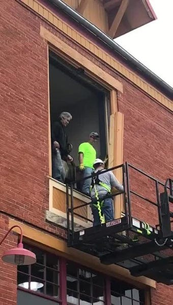 A construction crew removes a third-story window before extracting a 2,000-pound commercial wood fire grill.