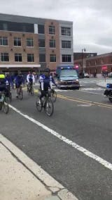Middlesex Borough Police Capt. Frank DeNick gets a kiss and encouragement  as the Police Unity Tour passes through Somerville