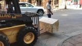 The first of 14 limestone benches is unloaded and placed by a city of Abilene crew May 14, 2019, at the corner of Cypress and North Second streets.