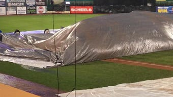 The grounds crew at Fox Cities Stadium battles wind to remove the tarp from the field before the Ozaukee vs. Markesan Division 3 state semifinal game.