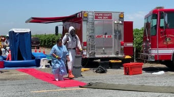 Tulare County Hazmat crews have started a mass decontamination of 63 field workers sprayed with a pesticide.