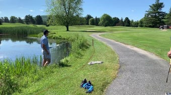 Dustin Perry takes off his shoes to attempt a shot from the hazard on the fourth hole at Williston Golf Club during a Vermont Amateur qualifier.