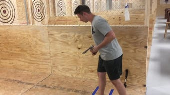 The owner of Grizzly Axes, the new ax-throwing bar coming to Pensacola, demonstrates proper ax-throwing form at his new facility on North Davis.