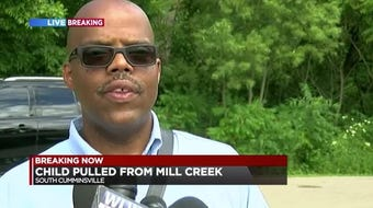 Firefighters rescued an 8 or 9-year-old child from the waters of the Mill Creek at the scene of a reported drowning.