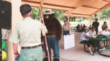 Smokey Bear presents Bill Tucker with a staff honoring his 29 seasons with the Smokey Bear Ranger District.